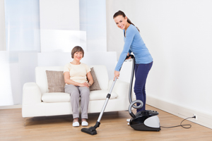 Housekeeper vacuuming for her client.